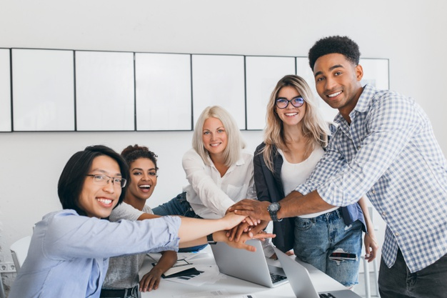 charming-blonde-employee-having-fun-with-colleagues-posing-photo-light-room-team-it-specialists-ended-big-hard-business-project-shaking-hands_197531-3738